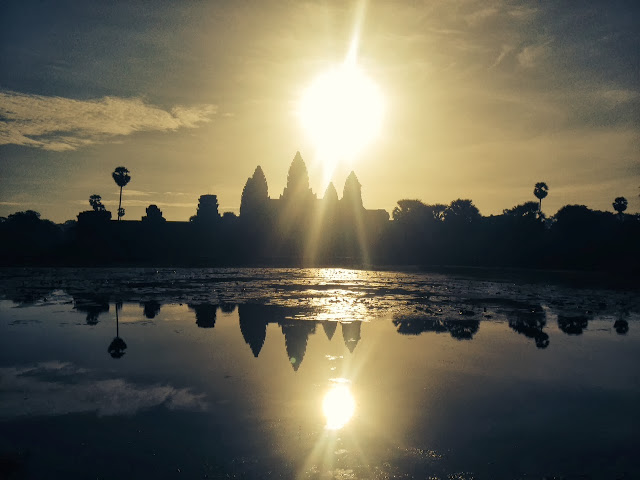 the sun rises behind the khmer spires of Angkor Wat, Cambodia