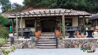 Base de pedra na construção de cabana rústica com os pilares de madeira com eucalipto tratado, a escada de dormente e o pergolado de madeira em frente.