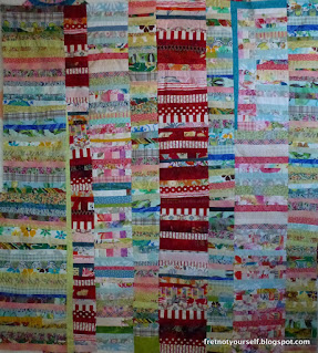 Red, pink, blue, and green fabrics create this Chinese Coin quilt