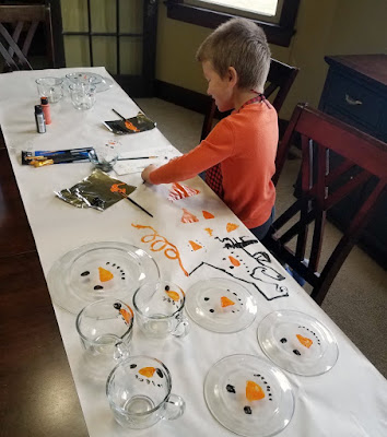 kid painting plates, mugs and the dropcloth paper