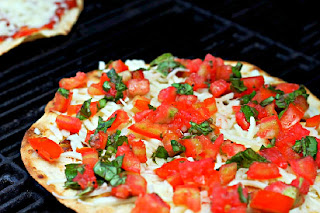 pizza on the grill with tomatoes and fresh basil