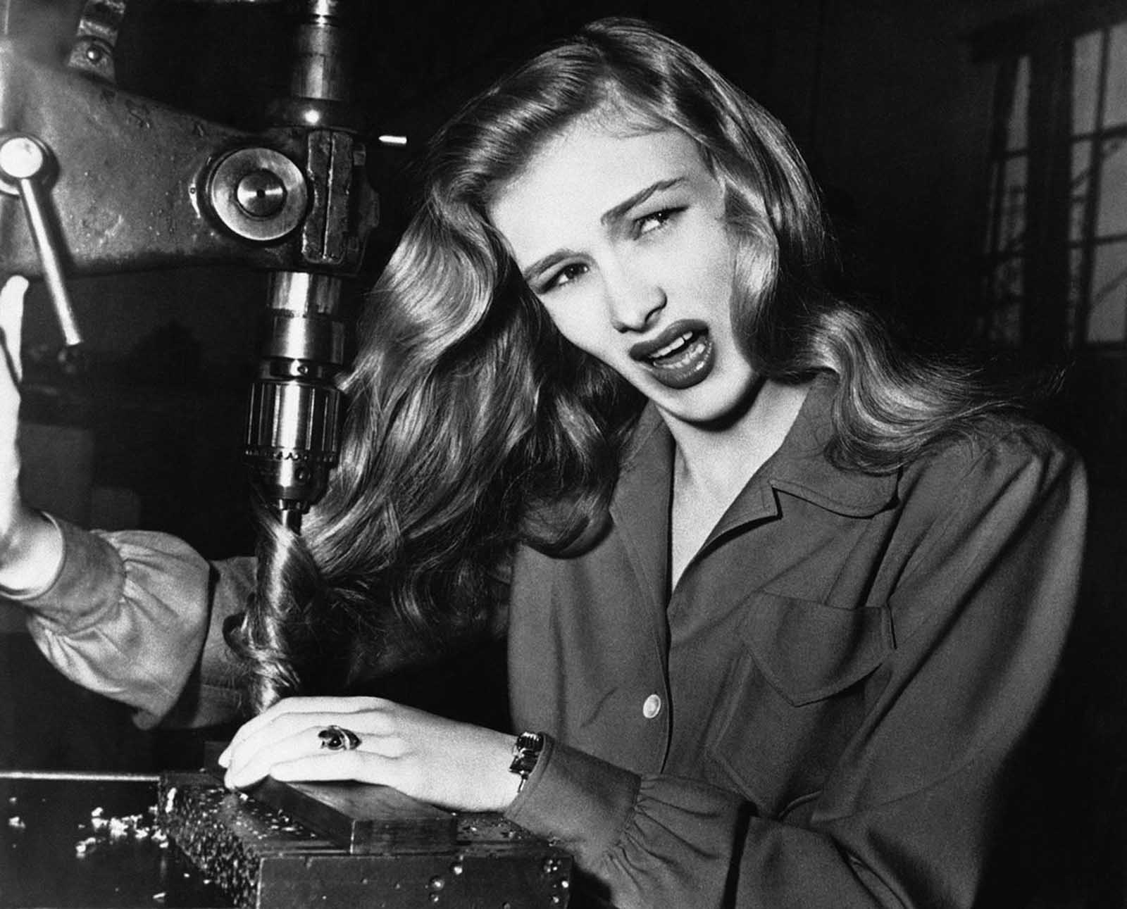 American film actress Veronica Lake, illustrates what can happen to women war workers who wear their hair long while working at their benches, in a factory somewhere in America, on November 9, 1943.