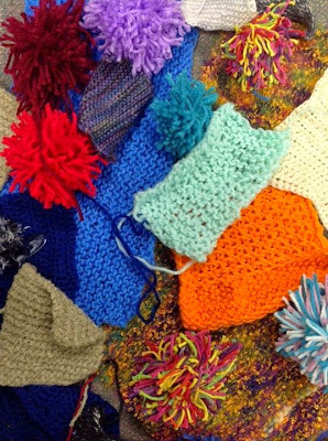 Pile of knitted swatches and pieces in assorted colors and textures
