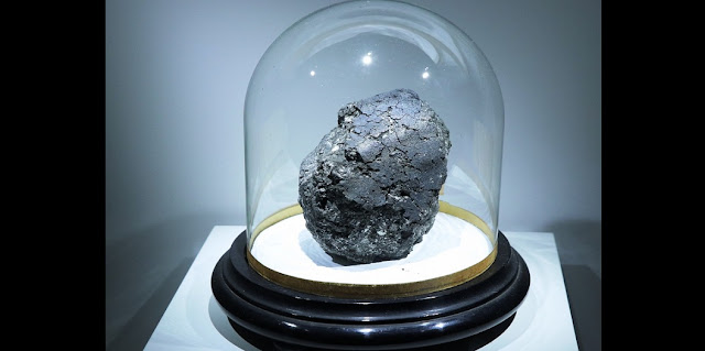 This is the Orgueil carbonaceous meteorite, a scientific treasure that fell in 1864 in southwest France. The main mass of the meteorite can be seen at the meteorite exhibit at the Muséum National d'Histoire Naturelle in Paris until January 2019. The stand on which the meteorite is displayed is about 30 cm across. Credit: K.H. Joy