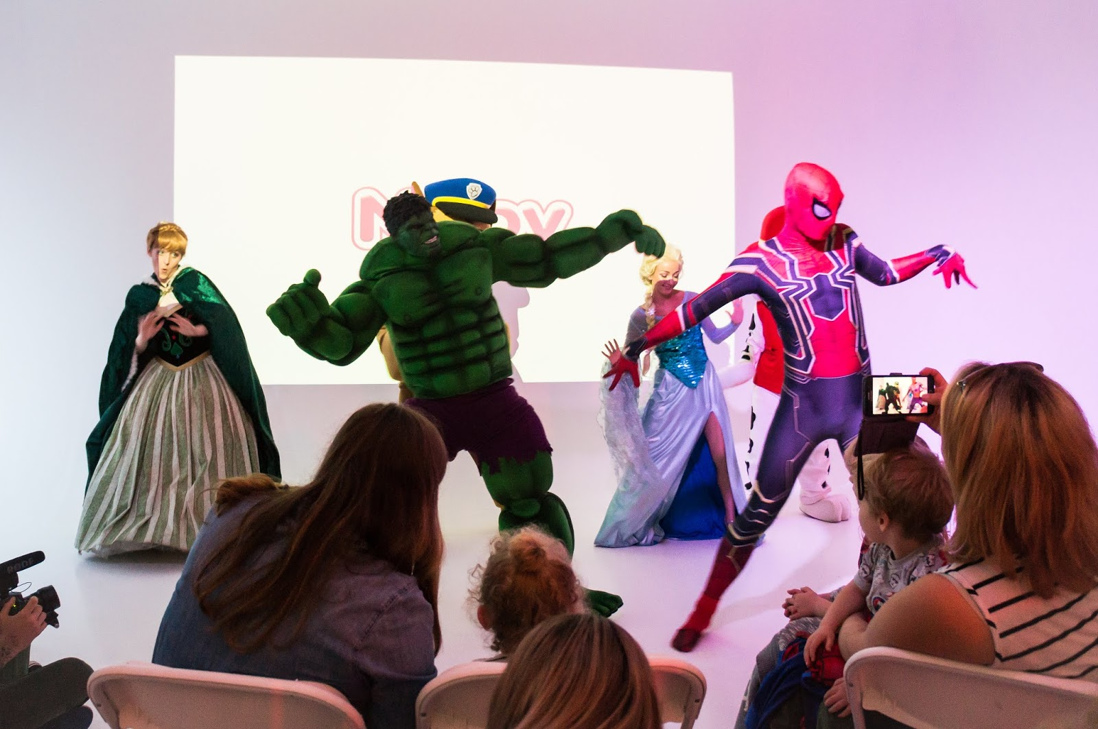 life size cartoon characters performing dance routine with parents and children watching at nuby big reveal event