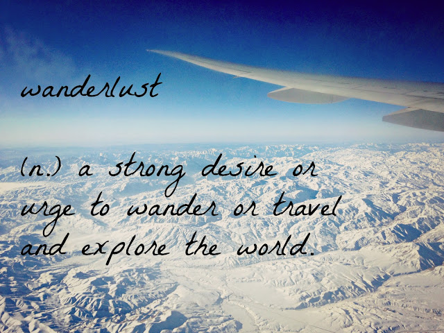 Wanderlust definition on background of snowy scene out an airplane window