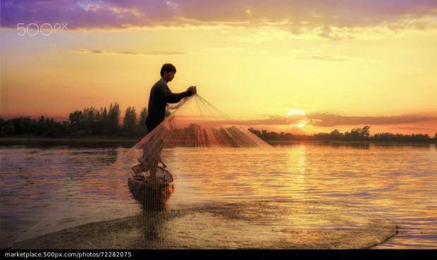 Homem pescando e sol nascendo