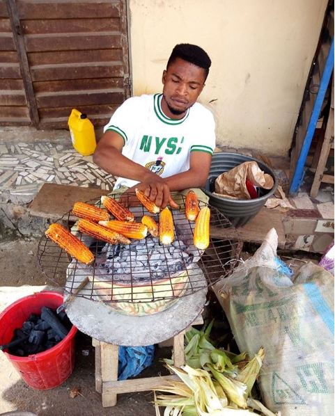 NYSC Member Roasting Corn On The Street Trend Online