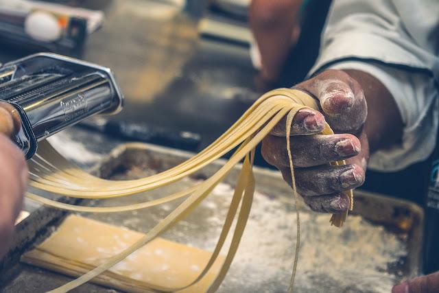 Cook preparing delicious pasta
