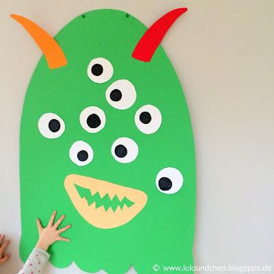 Monster aus buntem Tonpapier an der Wand mit Hörnern und Augen