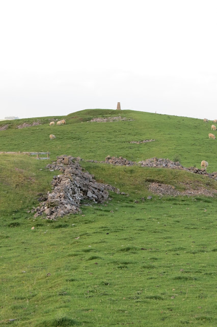 A steep hillside, with exposed rock, and the OS trig pillar at the top.