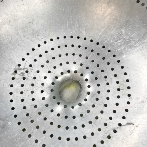 Using tin snips to cut a hole in an aluminum colander to make a light