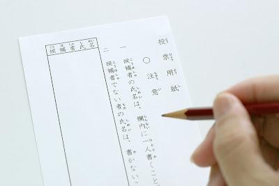 投票用紙に鉛筆で候補者の名前を記入するところ