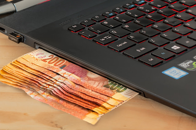 stack of cash next to laptop, money and dollar bills