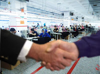 Bir dikim atölyesinde çalışanlar ve el sıkışıp anlaşan iş adamı ve ustabaşı