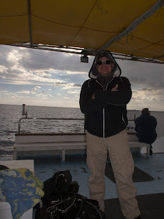 diver on a dive boat in his warm dry clothes