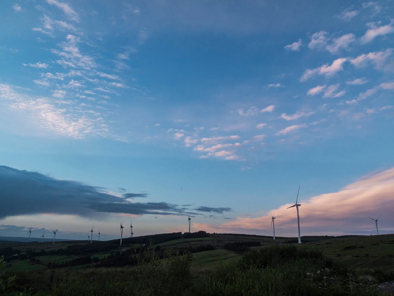 Windmills on top of a hill in the Boggeragh Mountains at sunset.