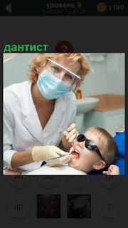 На приеме у дантиста в кресле сидит мальчик с открытым ртом, лечение зубов