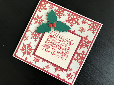 A hand made Christmas card with a stamped greeting and die cut holly decoration.