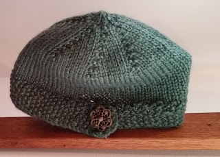 A knitted beanie in dark green. The crown is made with short rows, the body worked even and the brim is completed with a faux strap, finished with an ornate button.