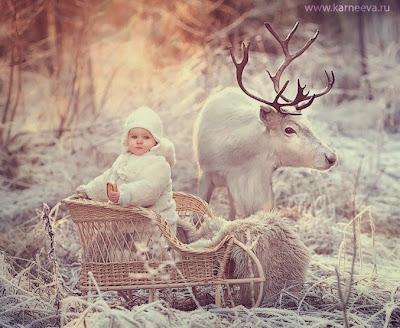 Niño y reno en la nieve