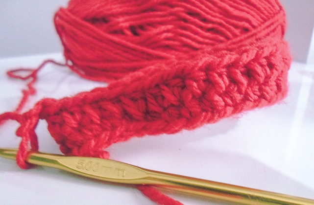 Foto de uma agulha de crochê dourada em primeiro plano, ao fundo, um novelo de lã vermelho com algumas carreiras de crochê prontas