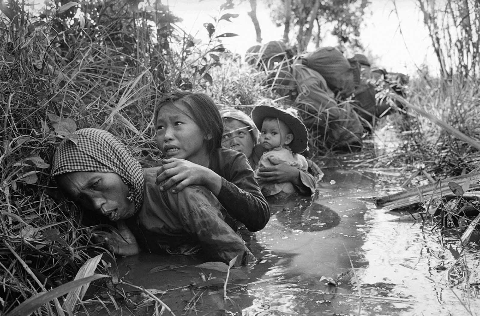 Women and children crouch in a muddy canal as they take cover from intense Viet Cong fire at Bao Trai, about 20 miles west of Saigon, on January 1, 1966. Paratroopers, background, of the U.S. 173rd Airborne Brigade escorted the South Vietnamese civilians through a series of firefights during the U.S. assault on a Viet Cong stronghold.