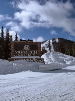 Sun shinning above the Monarch Mountain entrance sign, with the ski area in the distance all covered in snow