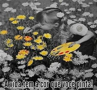 Foto em preto-e-branco de uma garotinha entre dezenas de calêndulas. Ela tem cabelo com franja, repartido ao meio, preso em Maria Chiquinha com uma flor; usa um macacão sobre a blusinha de manga curta. A menina  está com o corpo inclinado a frente, com a mão esquerda segura a paleta de cores e com o pincel na outra mão, pinta uma flor em amarelo, algumas outras já foram pintadas também em amarelo e outras  em amarelo e vermelho; e amarelo e laranja. No rodapé, lê-se: A vida tem a cor que você pinta!