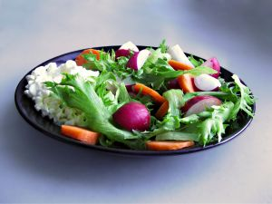 Image: Light radish salad: Salad on black plate with some cottage cheese, carrots and radish, by typofi on freeimages