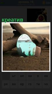 на берегу около коряги на песке лежит креативная лампочка