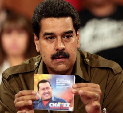Nicolás Maduro triste mostrando la imagen de Hugo Chávez