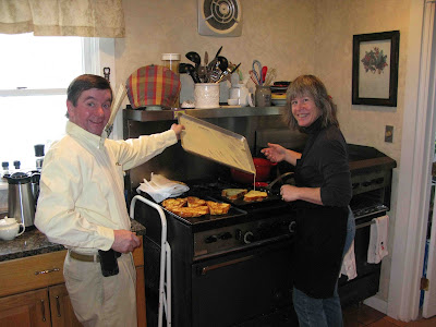 Smiling couple before a large stove frying french toast