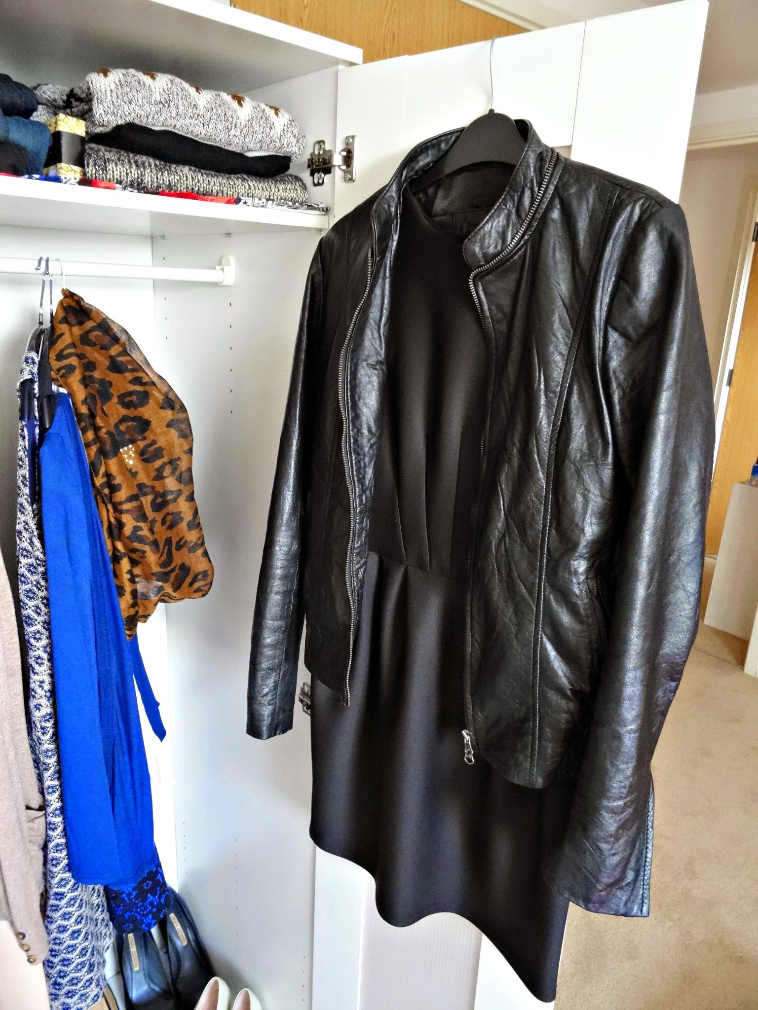 Leather jacket and dress on a hanger