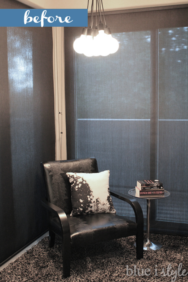 Black chair in front of black solar shades on sliders