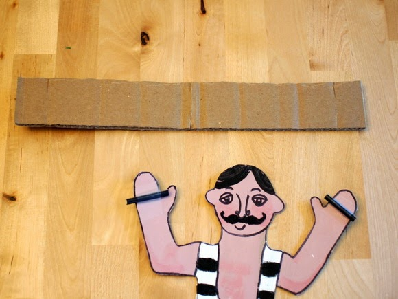Add straws to the man's hands and cut out a cardboard rectangle
