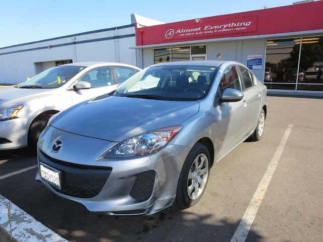 Scraped bumper on 2013 Mazda 3 before collision repairs at Almost Everything Auto Body.