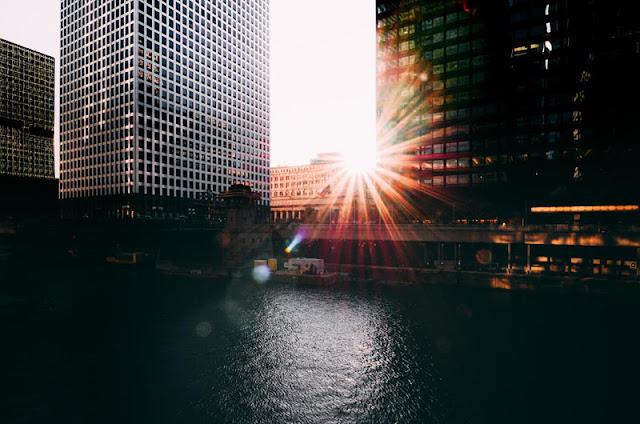 Sole al tramonto tra due palazzi fotografato con la Leica TL