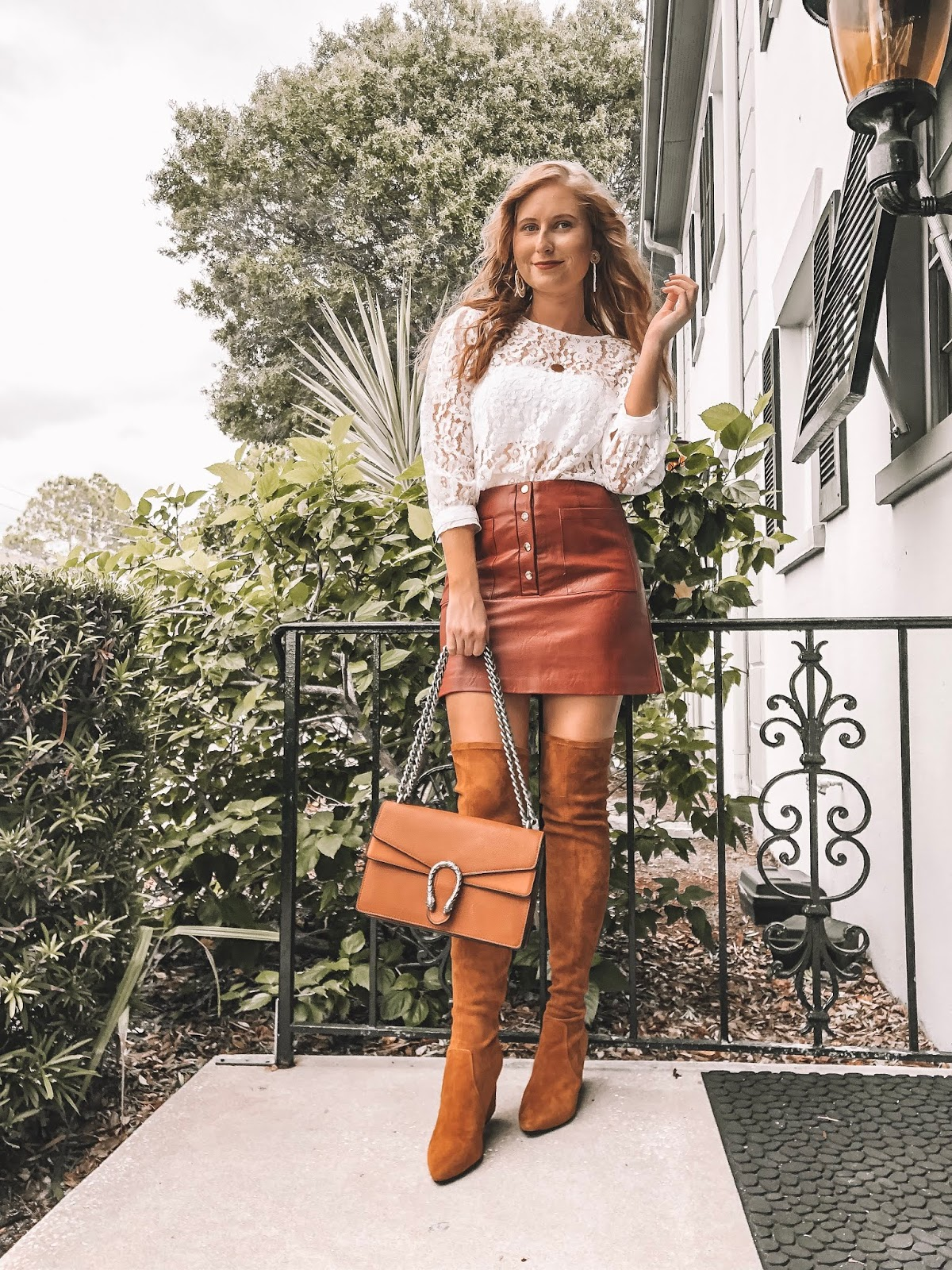 Tampa blogger Amanda Burrows is wearing an outfit for Thanksgiving. Her skirt is faux leather and her top is white and has lace. Her over the knee boots are from Goodnight Macaroon and make her legs look really long.