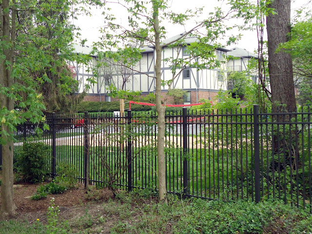 Large tudor-style apartment building amid trees, behind wrought-iron fence.