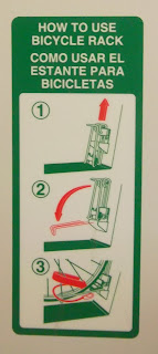 Instructional sign displaying how to secure lower wheel of bicycle in SMART Train bike-storage compartment