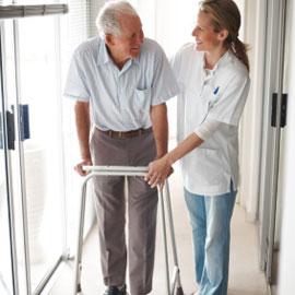 joven ayudando a anciano a caminar con andadera