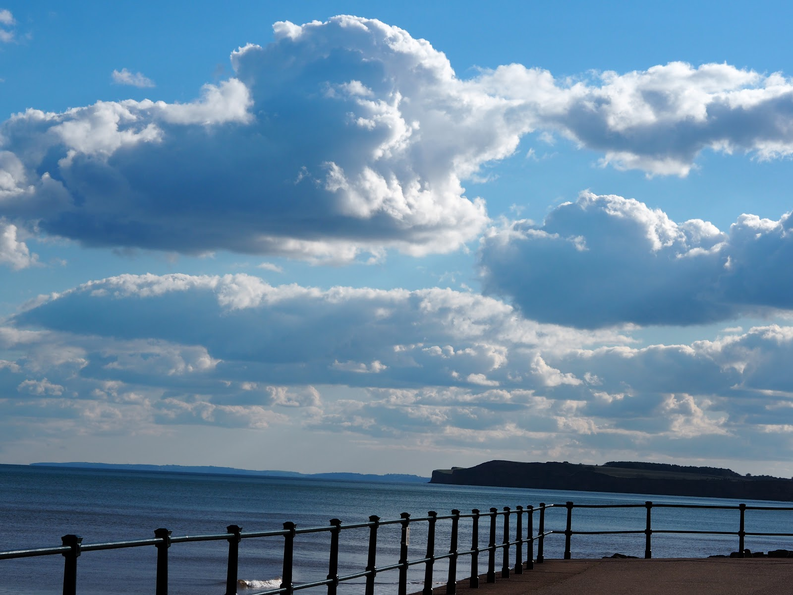 Bright blue sky with clouds at Sidmouth beach