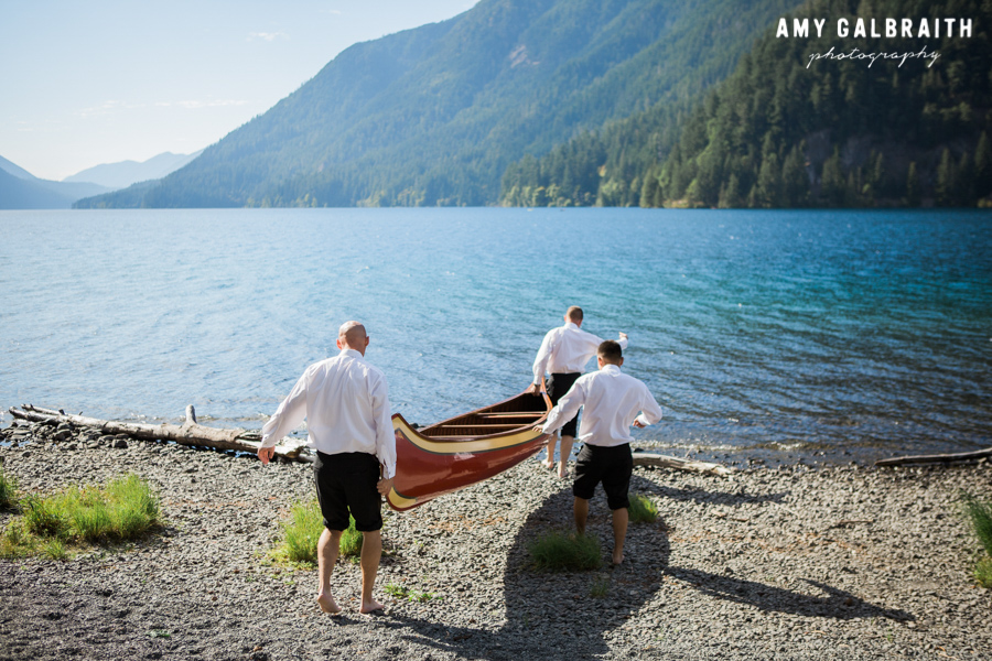 groomsmen putting canoe in lake