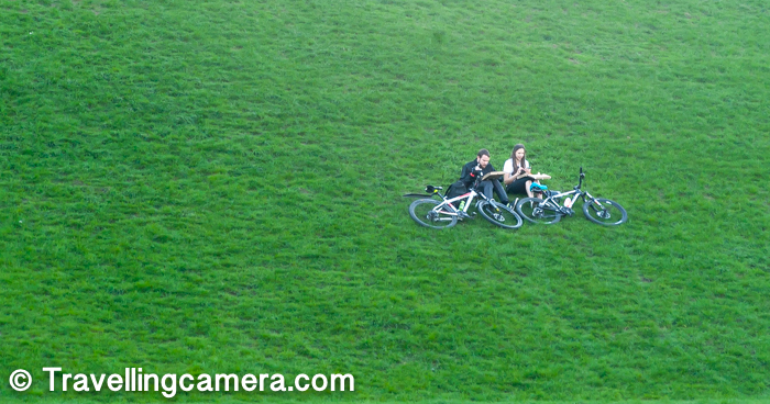 Above photograph shows 2 cyclists taking a break on elevated lawn and enjoying their meal after a ride (probably). They were sitting at quite a high point and I was wondering if they rode the bikes to this point or hiked to this point by lifting the bikes on their shoulders. The second option sounds more reasonable.