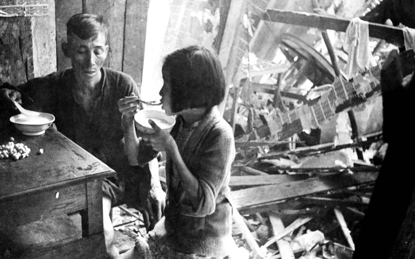 Dining together after a Japanese raid in the Singapore area, on February 26, 1942. A Chinese man and his young daughter sit calmly amid the ruins eating bowls of rice.