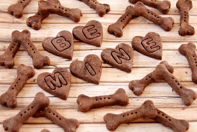 "Homemade Valentine's Day dog treats shaped like hearts stamped with letters reading ""BE MINE"" on a table surrounded by bone shaped treats"