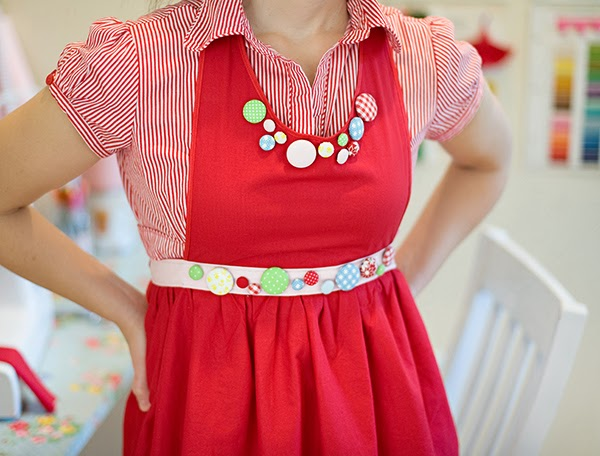 Farm Chicks handmade red apron with fabric covered buttons - At work! Look at those fabulous wedge shoes! I'm quite a big fan of the vintage catalogue cards on the wall with all the different colours.    I've also just spotted some more old school Cath Kidston patterns in the top corner, on the shelf there are some cake tins that are all stacked quite neatly!    It's quite clear that CK had a big part to play in this craft room, she has had a big part to play in the inspiration for my own craft room but I've gone for the light pastels instead of reds and bold patterns.