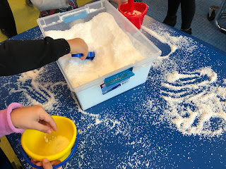 kids scooping and playing with artificial snow on table