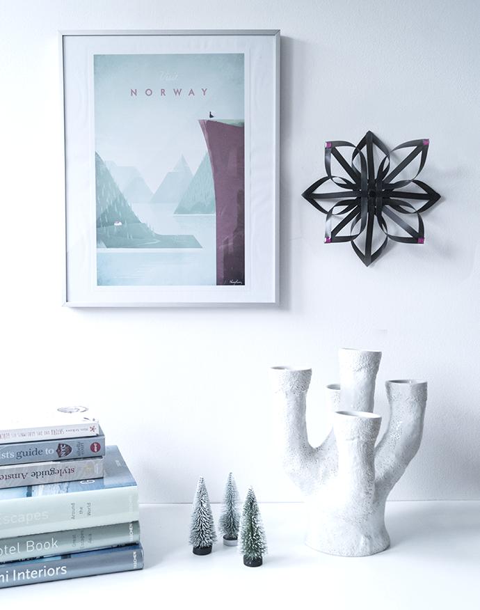 Schwarzer Stern hängt an der Wand neben einem Bild über Norwegen.